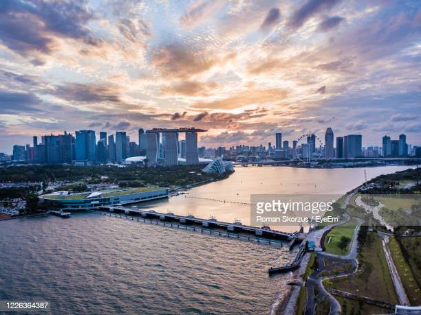 scenic aerial drone picture of the skyline of marina bay in singapore during sunset - marina bay singapore stock pictures, royalty-free photos & images