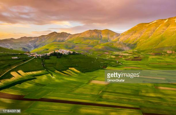 scenic aerial view of a countryside landscape with lots of patchwork fields and beautiful green rolling hills, castelluccio, umbria, italy - umbria stock pictures, royalty-free photos & images