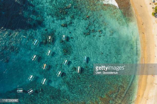 scenic aerial view of a lot of boats on the  seaside on nusa penida - nusa penida stock pictures, royalty-free photos & images