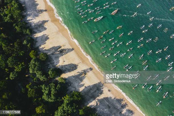 scenic aerial view of a lot of fishing boats in lagoon on java - fishing boat stock pictures, royalty-free photos & images