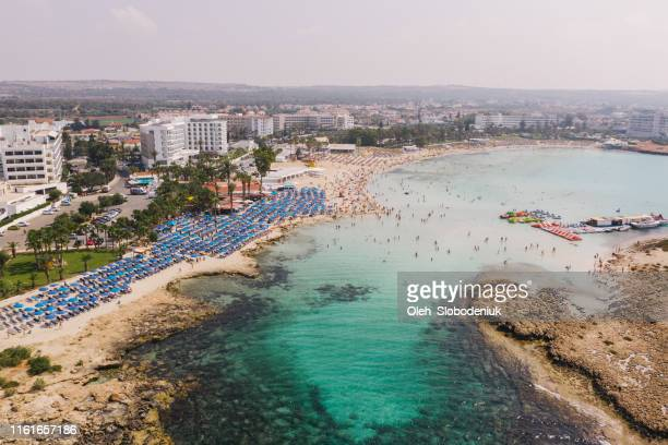 scenic aerial view of beach with blue umbrellas on cyprus - republic of cyprus stock pictures, royalty-free photos & images