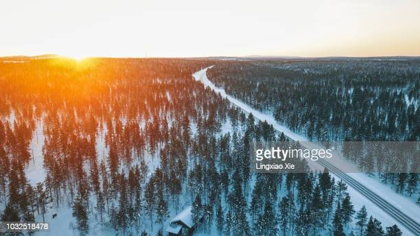 scenic aerial view of beautiful sunrise over forest and road in winter, lapland, finland - finland stock pictures, royalty-free photos & images