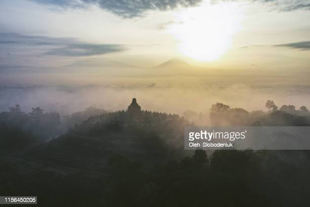 scenic aerial view of borobudur temple at sunrise in fog - wonderlust stock pictures, royalty-free photos & images