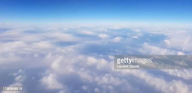 scenic aerial view of cloudscape - a clear blue sky above the clouds - laurent sauvel photos et images de collection