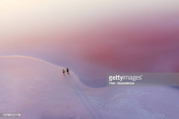 scenic aerial view of heterosexual walking on  pink salt lake - tranquility stock pictures, royalty-free photos & images
