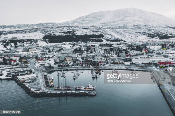 scenic aerial view of port with old ships in husavik, in winter - husavik stock photos and pictures
