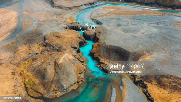 scenic aerial view of the car parking at the remote turquoise waterfall in the mountain canyon in iceland - iceland stock pictures, royalty-free photos & images