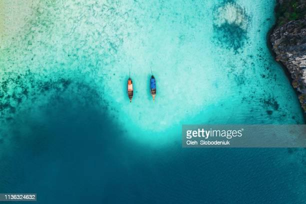 szenische luftaufnahme von zwei booten auf see in thailand - asiatisches langboot stock-fotos und bilder