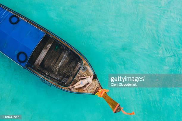 szenische luftaufnahme der frau, die auf einem langen schwanzboot auf dem meer liegt - asiatisches langboot stock-fotos und bilder