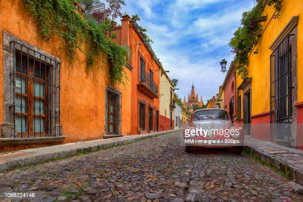 scenic cobbled street with car and church in background - mexique photos et images de collection