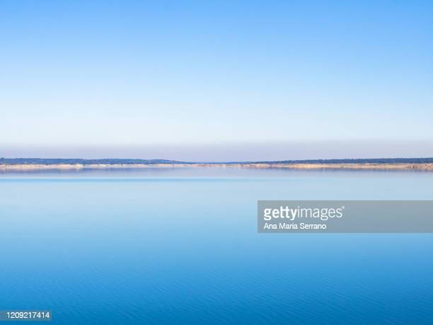 scenic landscape of the horizon with clear sky and calm water at the la almendra reservoir next to the la almendra dam - rivage photos et images de collection
