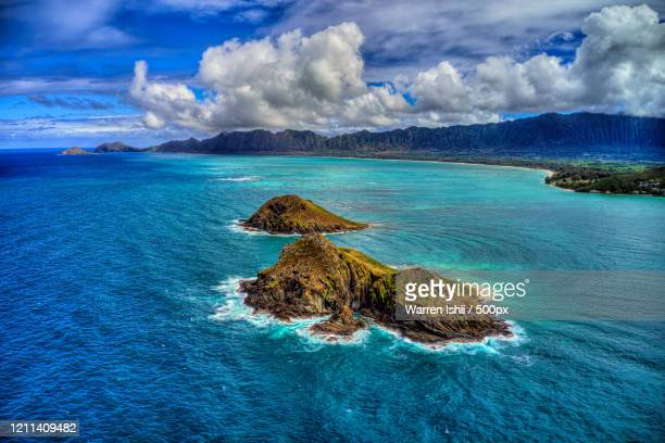 scenic landscape with small rocky na mokulua islands with lanikai in background, kailua, hawaii, usa - kailua stock pictures, royalty-free photos & images