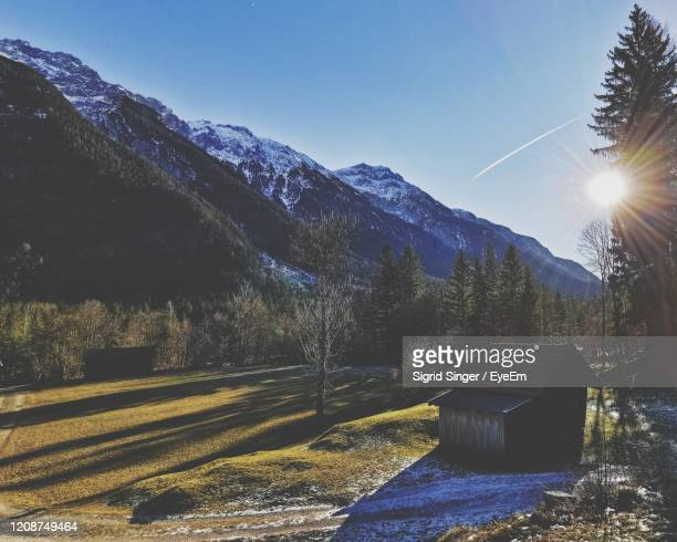 scenic mountain view against sunlight in the karwendel region with a hut - mittenwald stock pictures, royalty-free photos & images