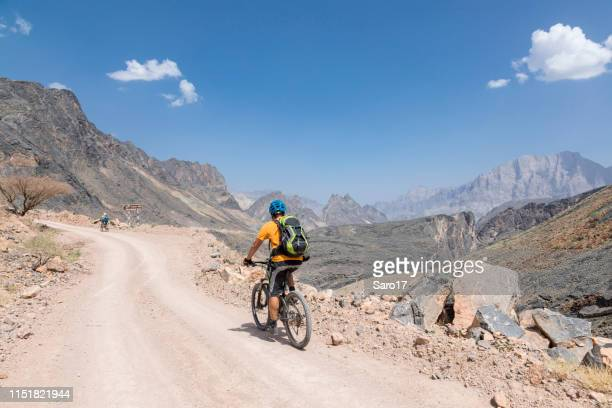 scenic mountainbiking on gravel roads, oman. - muscat governorate stock pictures, royalty-free photos & images