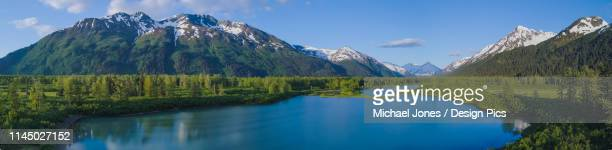 a scenic of the waterways in portage valley, alaska on a sunny summer evening  with the snow-capped chugach mountains reflecting in the calm water. - chugach mountains stock pictures, royalty-free photos & images