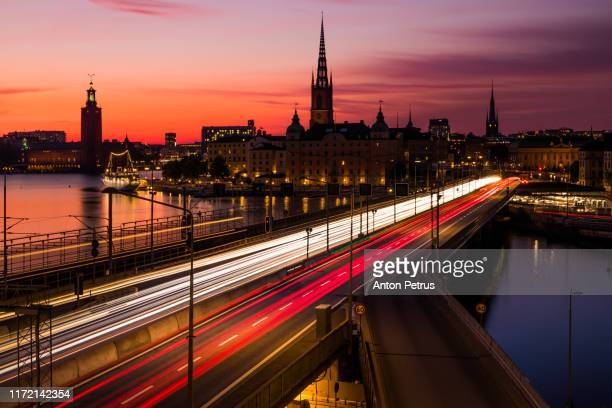scenic panoramic view of gamla stan, view of old buildings and car traffic at the bridge stockholm, sweden - stockholm stock pictures, royalty-free photos & images