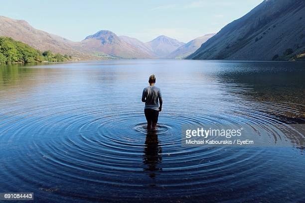 scenic rear view of young woman walking in lake - rippled stock pictures, royalty-free photos & images