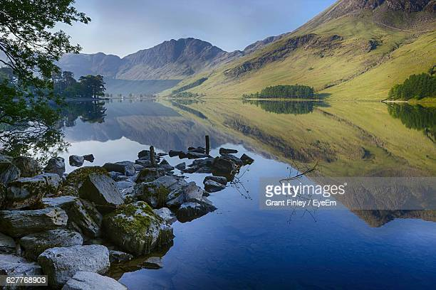 Scenic Reflection Of Green Landscape In Calm Lake