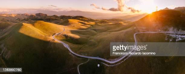 scenic road at sunset in campo imperatore, abruzzo, italy. aerial view - campo imperatore foto e immagini stock