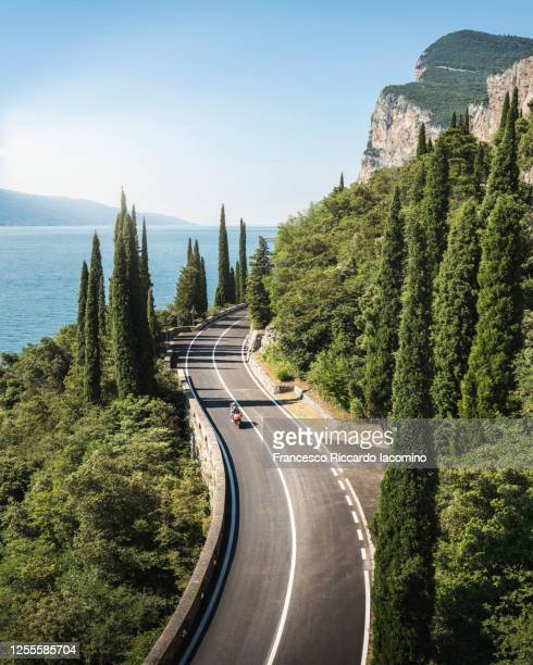 scenic road on lake garda in summertime, blue water and sky. italy - iacomino italy foto e immagini stock