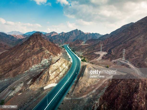 scenic road through hajar mountain range stretching through uae and oman - ras al khaimah stock pictures, royalty-free photos & images