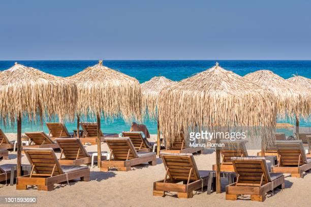 scenic seascape of agioi saranda beach, with straw umbrellas beach and beach lounge chairs, pelion peninsula, magnesia, aegean sea, greece. - mediterranean culture stock pictures, royalty-free photos & images
