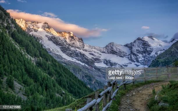 scenic snowcapped mountain landscape at sunrise, valnontey, cogne, gran paradiso national park, italy - parco nazionale del gran paradiso foto e immagini stock