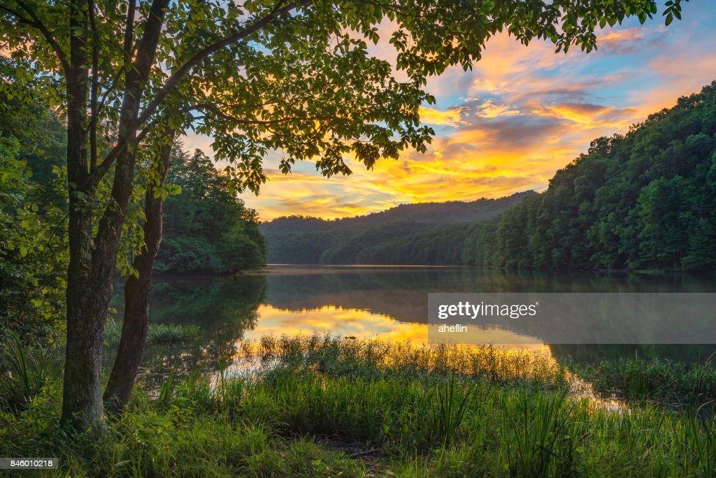 Scenic summer sunset over calm mountain lake : Stock Photo