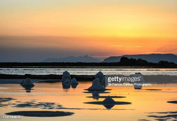 scenic sunset with medieval salt pans in mediterranean lagoon in marsala, sicily, italy - marsala sicily stock pictures, royalty-free photos & images