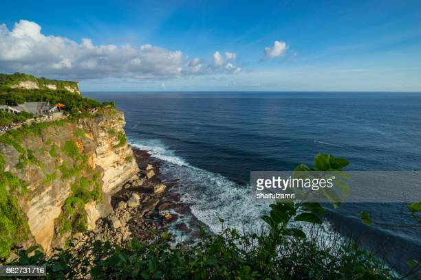 a scenic uluwatu cliff with pavilion and blue sea in bali, indonesia. - shaifulzamri stock pictures, royalty-free photos & images