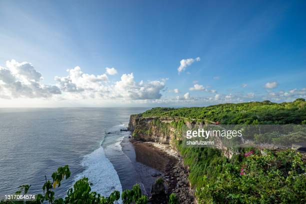 a scenic uluwatu cliff with pavilion and blue sea in bali - shaifulzamri stock pictures, royalty-free photos & images