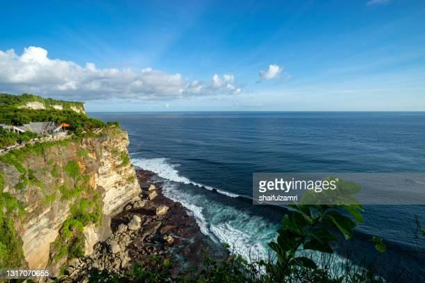 a scenic uluwatu cliff with pavilion and blue sea in bali - shaifulzamri foto e immagini stock