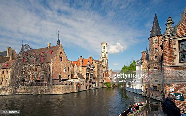 CONTENT] Scenic view along a Bruges canal showing medieval structures and church tower