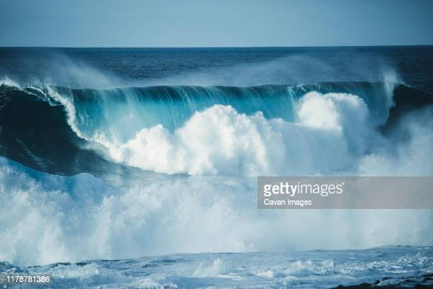 scenic view of a big wave breaking in the sea against clear sky - colliding stock pictures, royalty-free photos & images