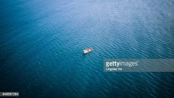 Scenic view of a boat sailing across the blue ocean at twilight
