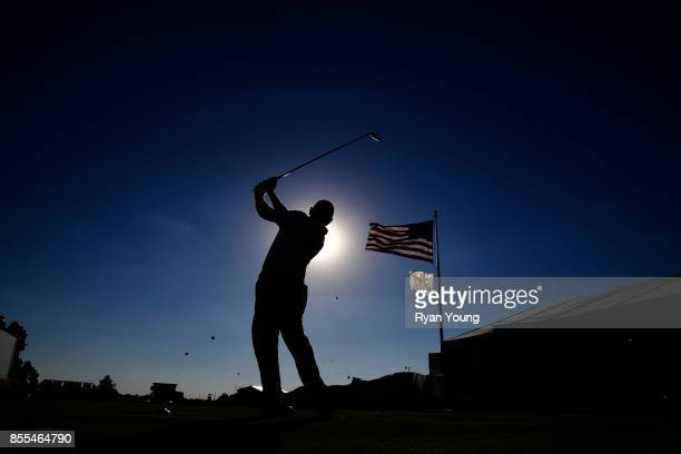A scenic view of a golfers silhouette hitting is seen with the US Flag during the first round of the Presidents Cup at Liberty National Golf Club on...