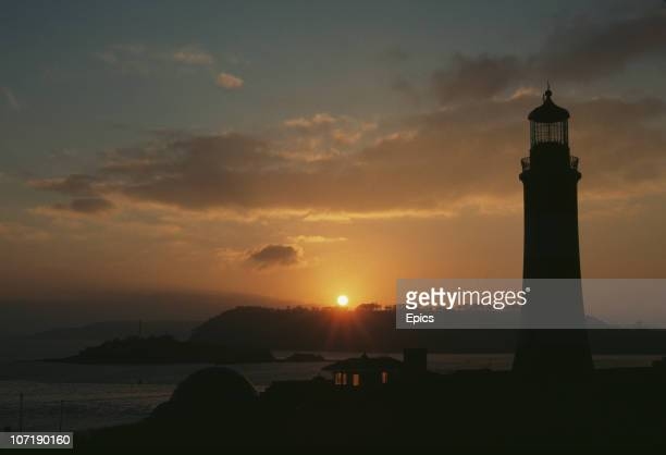 A scenic view of a sunset over Smeaton's tower a lighthouse on the coast of Plymouth Hoe Plymouth Devon December 1989