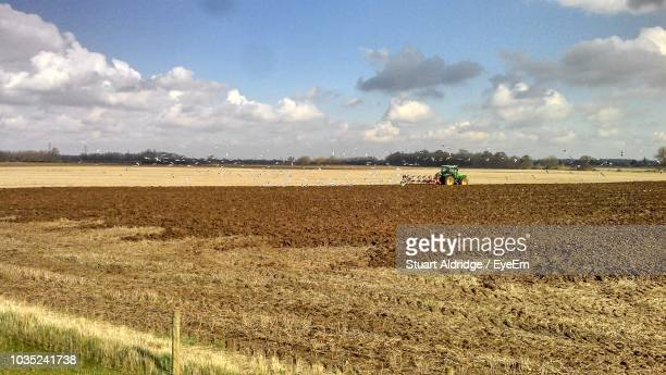 Scenic View Of Agricultural Field Against Cloudy Sky