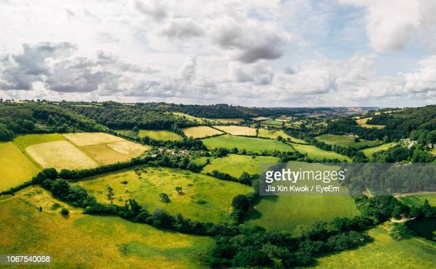 scenic view of agricultural field against cloudy sky - overhemd en stropdas stock pictures, royalty-free photos & images