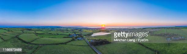 scenic view of agricultural field against sky during sunset - northern ireland stock pictures, royalty-free photos & images