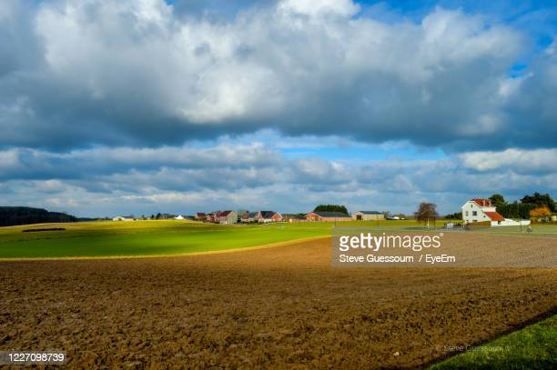 scenic view of agricultural field against sky - moody sky stock pictures, royalty-free photos & images