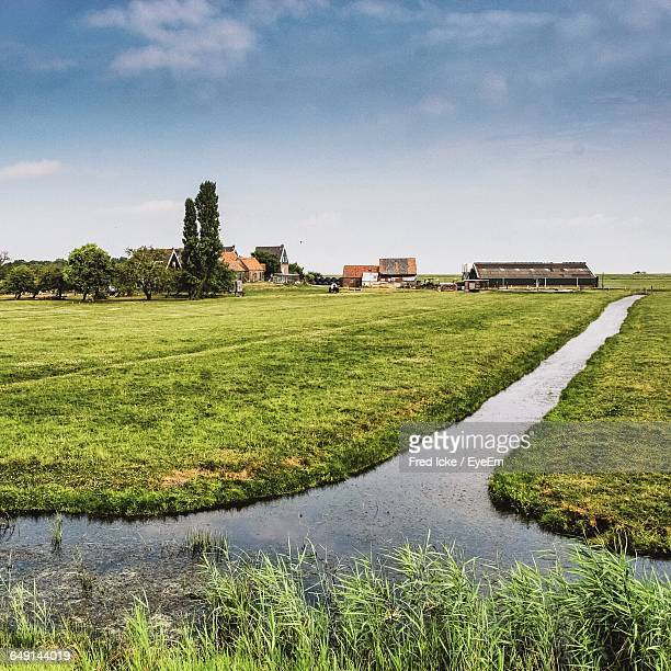 scenic view of agricultural field against sky - ditch stock photos and pictures