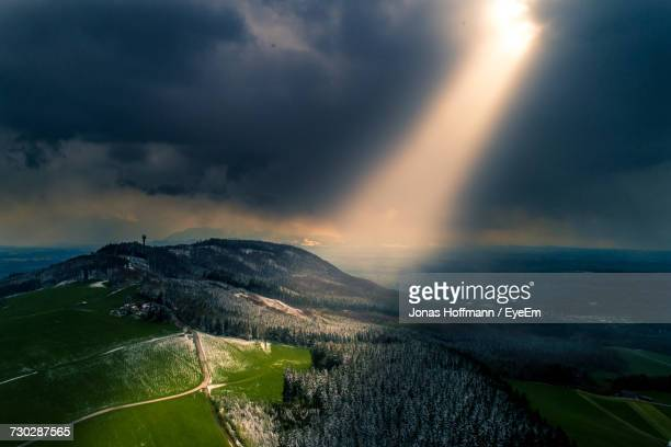scenic view of agricultural field against storm clouds - zonnestraal stockfoto's en -beelden