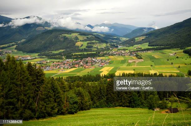 scenic view of agricultural field by mountains against sky - ヴァルダーオラ ストックフォトと画像