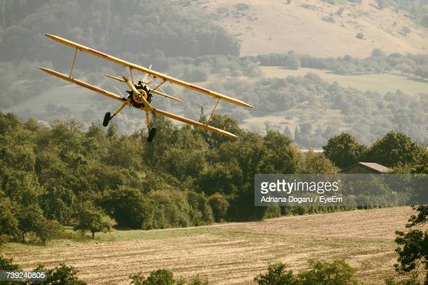 Scenic View Of Airplane Flying Above Field
