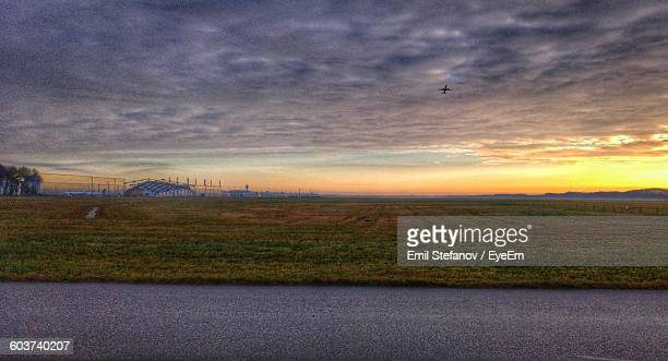 scenic view of airplane flying over field against overcast sky at munich international airport - munich airport stock photos and pictures