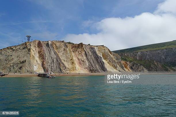 scenic view of alum bay by rock formation against sky - alum bay stock pictures, royalty-free photos & images