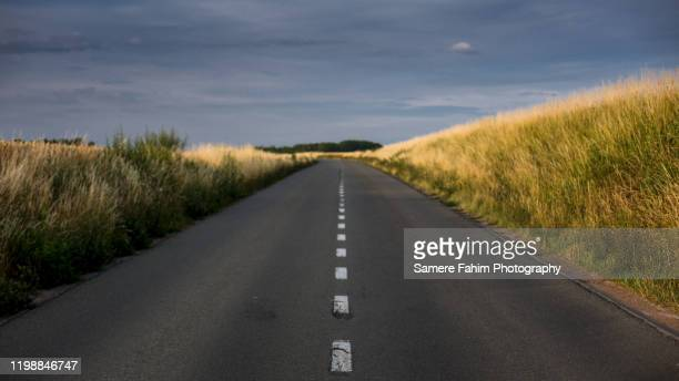scenic view of an empty road amidst fields against sky - benelux stockfoto's en -beelden