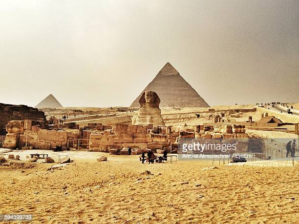 scenic view of ancient egyptian features against clear sky - giza pyramids stock pictures, royalty-free photos & images