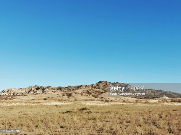 scenic view of arid landscape against clear blue sky - 荒野 ストックフォトと画像
